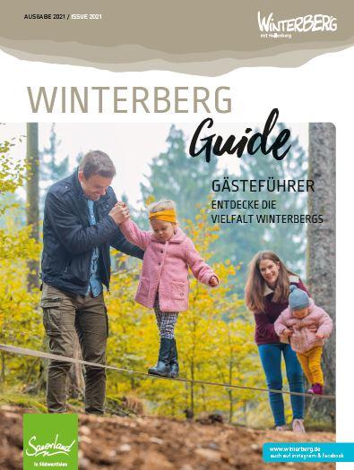 Die Titelseite des Winterberg Guide 2021 zeigt eine Familie mit zwei Kindern im Wald.